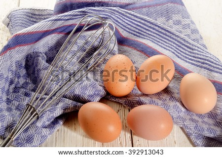 brown free range eggs and a whisk on kitchen towel - stock photo
