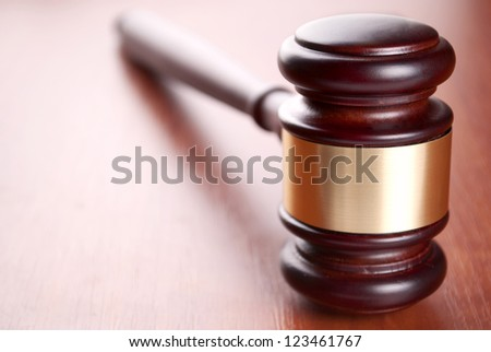 brown gavel with a brass band on a brown background - stock photo