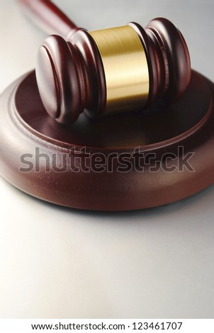 brown gavel with a brass band on a gray background - stock photo