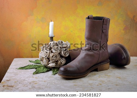 Brown genuine haft boots on grunge with dry flowers and candles still life art photography - stock photo