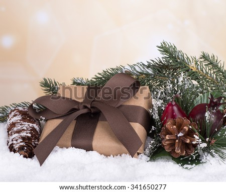 Brown gift box with Christmas ornaments on snow with colorful holiday background - stock photo