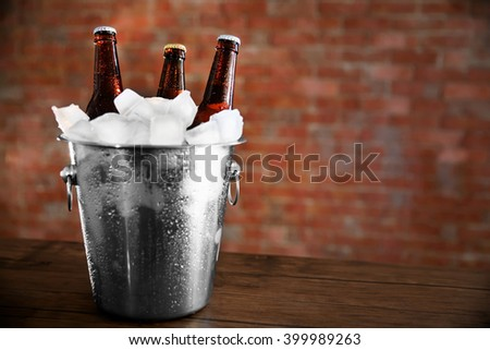 Brown glass bottles of beer in ice-pail on brick wall background - stock photo