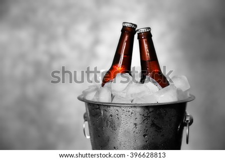 Brown glass bottles of beer in ice-pail on grey background - stock photo
