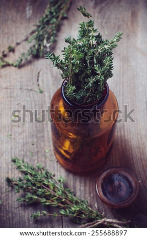 Brown glass pharmacy bottle and thyme herb in vintage style on old wooden board. - stock photo