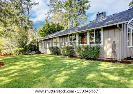 Brown grey house exterior with spring backyard. - stock photo