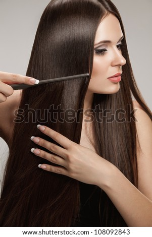 Brown Hair. Beautiful Woman combs her Healthy Long Hairr. High quality image. - stock photo