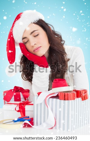Brown hair in santa hat napping against blue background with vignette - stock photo