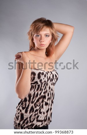 brown-haired girl dressed in a tiger, leopard fabric poses in the studio - stock photo