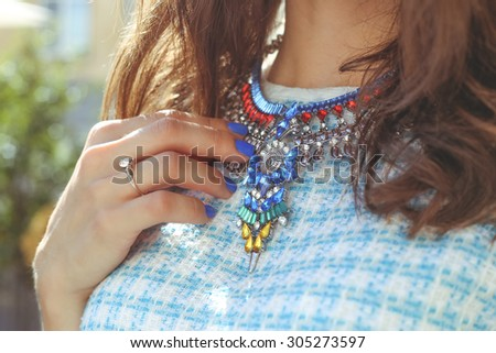 Brown-haired girl in a blue dress with a necklace. Large necklace rhinestones. Thin hand with blue nail. Fashion trends. Street fashion. Trendy, stylish. Fashionable girl. - stock photo