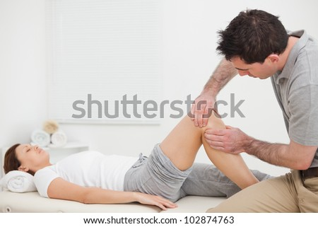 Brown-haired man massaging the knee of a woman in a room - stock photo