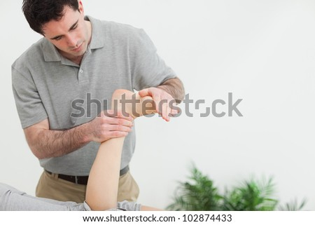 Brown-haired therapist stretching the foot of a patient in a room - stock photo