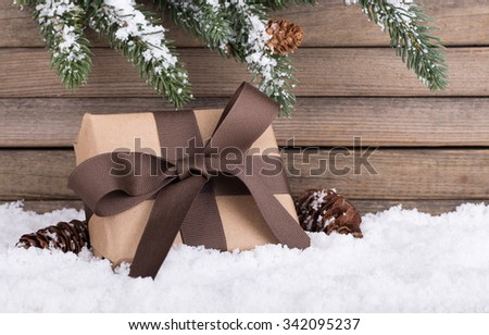 Brown holiday gift box on snow with a wood background - stock photo