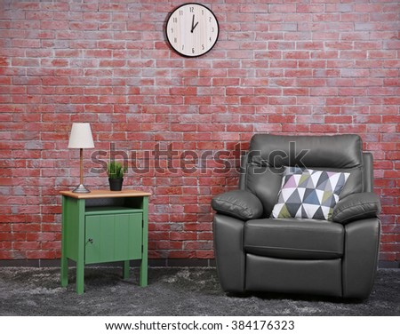 Brown leather armchair and green small table against brick wall background - stock photo
