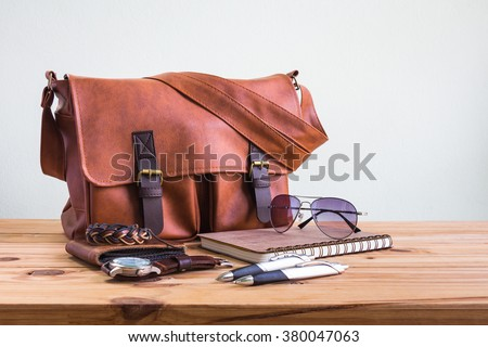 Brown leather bags with men's accessories on wooden table over wall background - stock photo