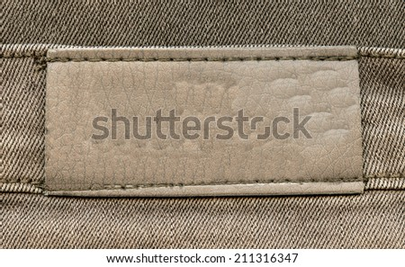 brown leather label on textile background  - stock photo