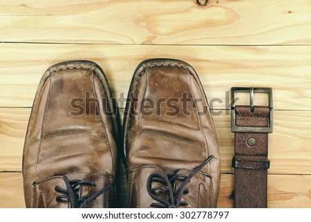 Brown leather men's shoes and belt on a wooden board. Men fashion. Men accessories. HDR.  - stock photo