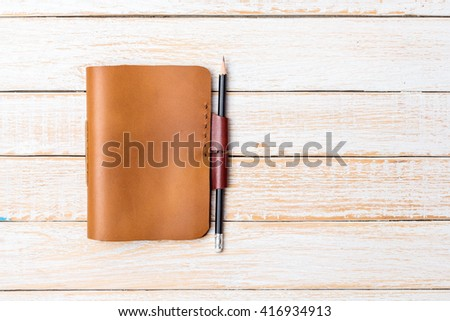 Brown Leather notebooks with pencil on white wooden background - stock photo