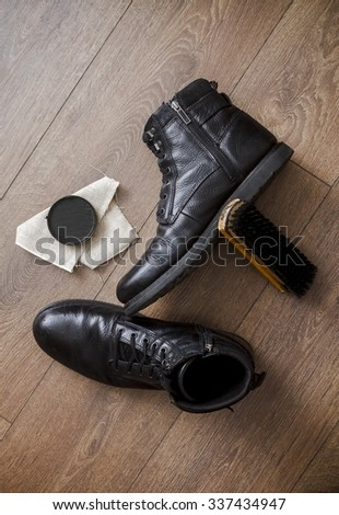 Brown leather shoes on a wooden floor with brush and cream - stock photo