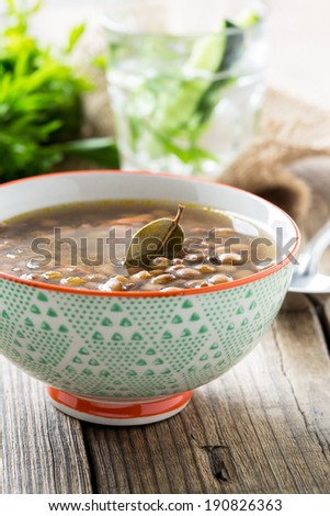 Brown lentil soup with mushrooms in bowl on wooden table - stock photo