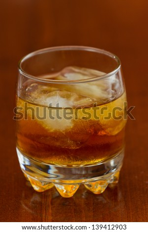 brown liquor served on the rocks on a busy bar with a shallow depth of field - stock photo