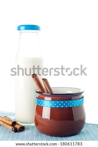 Brown mug, milk bottle, cinnamon on blue napkin - stock photo