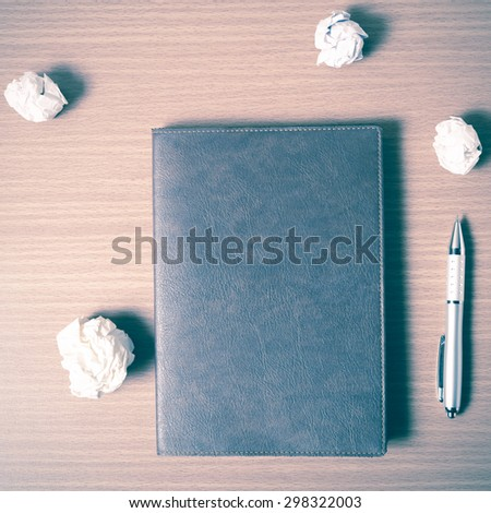 brown notebook and crumpled paper on wood background vintage style - stock photo
