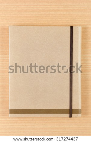 brown notebook on wooden background - stock photo