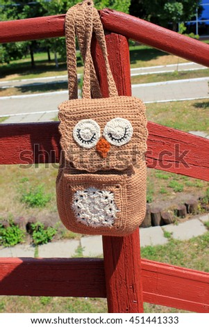 Brown Owl crochet Backpack for children hanging on a red fence. - stock photo