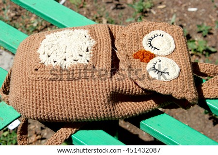 Brown Owl crochet Backpack for children lies on a green bench. - stock photo