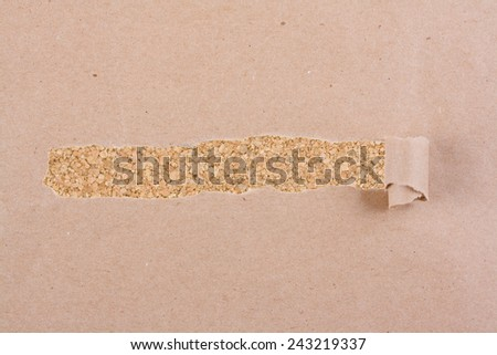 Brown package paper torn to reveal corkboard panel ideal for copy space. - stock photo