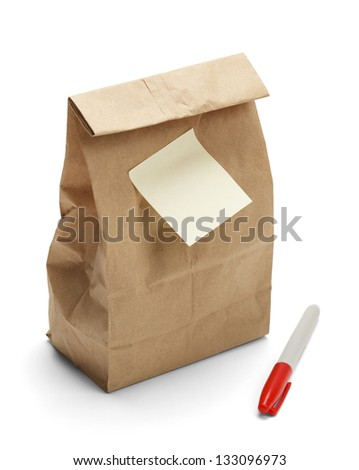 Brown Paper Bag Lunch with copy space and sticky note plus marker isolated on a white background. - stock photo