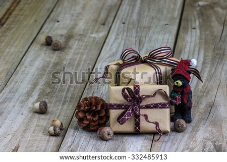 Brown paper packages tied in purple ribbon by acorns and bear ornament on antique rustic wooden background - stock photo