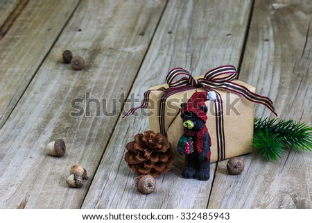Brown paper packages tied in purple ribbon by acorns, Christmas garland and bear ornament on antique rustic wooden background - stock photo