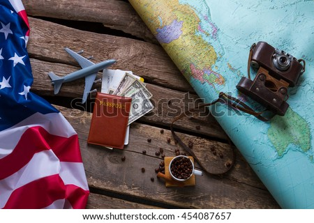 Brown passport and US flag. Photo camera on a map. Spend your vacation abroad. Visa to USA is opened. - stock photo