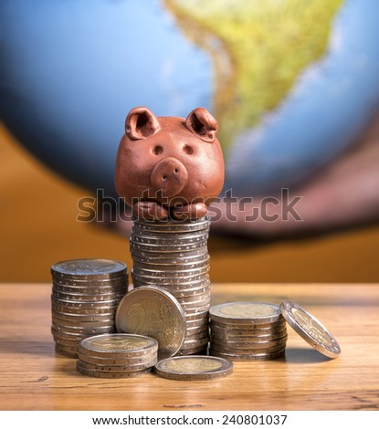 Brown piggy bank and coins, with earth background. - stock photo