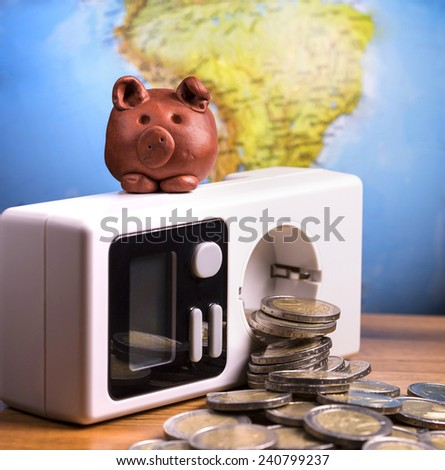 Brown piggy on white electric meter. - stock photo