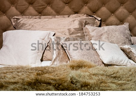 Brown pillows with furry duvet on the bed - stock photo