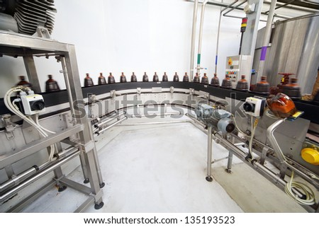 Brown plastic bottles with fresh beer go on conveyor belt at large brewery. - stock photo