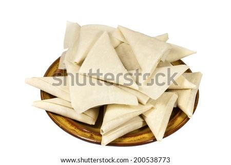 brown plate of freshly folded uncooked samosas - stock photo