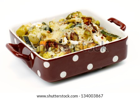 Brown Polka Dot Casserole Dish with Vegetables, Broccoli, Zucchini, Cream Cheese and Spices isolated on white background - stock photo