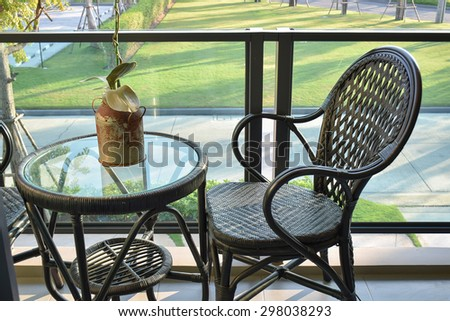 brown rattan chair on modern balcony overlooking a garden - stock photo