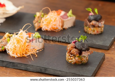 Brown rice and Jalapeno chili salsa topped with Hamachi, Carpaccio and Black garlic, and Aji ginger spicy (mackerel) and Akami tataki with ponzu sauce. - stock photo