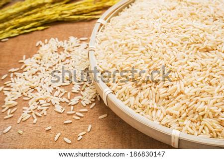 Brown rice on wicker basket - stock photo