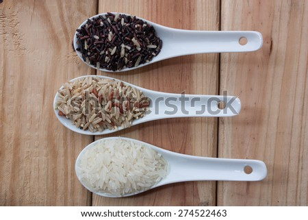 Brown rice or riceberry  in spoon on wood background - stock photo