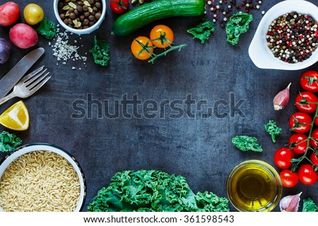 Brown rice with fresh delicious vegetables and ingredients for tasty cooking on vintage dark background. Top view. Diet or Sports nutrition concept. - stock photo