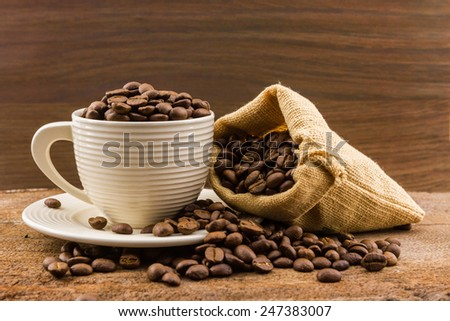 Brown roasted coffee beans in a canvas sack on wood background. - stock photo