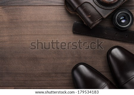 brown shoes and film camera on the wooden table - stock photo