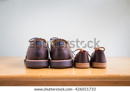 Brown shoes of daddy and son on on wooden table, bar or counter over gray wall background, fathers day   - stock photo