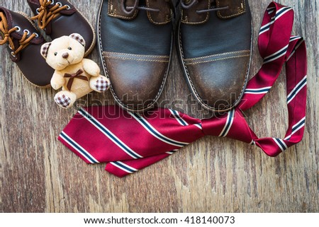 Brown shoes of father and son with brown teddy bear and red necktie on rustic wooden background, father's day concept - stock photo