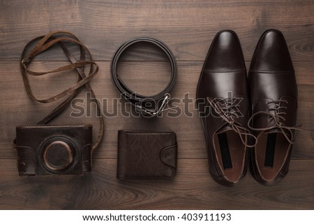 brown shoes, purse, belt, and film camera on wooden table - stock photo